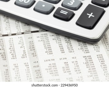 Calculator rest on stock price detail financial newspaper