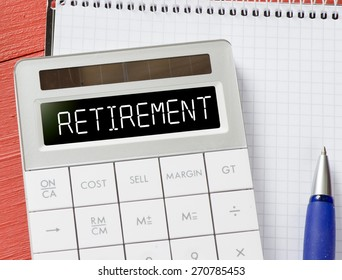 Calculator with retirement word.  Calculator with retirement word and notepad, pen on background