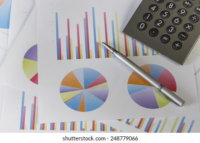 Calculator and a silver pen on a batch of colorful diagrams
