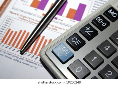 Calculator, steel pen and financial analysis report.