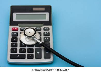 A calculator and stethoscope isolated on a blue background, calculating healthcare costs