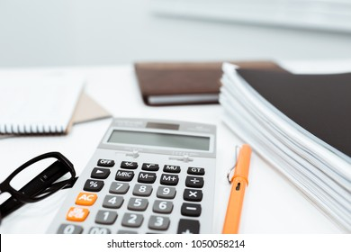 Calculator and tax business documents put on the desk in accountant office.
