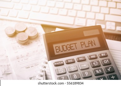 Calculator with text Budget Plan. Calculator, currency, book, bills and computer keyboard on wooden table. Business, finance, banking conceptual.