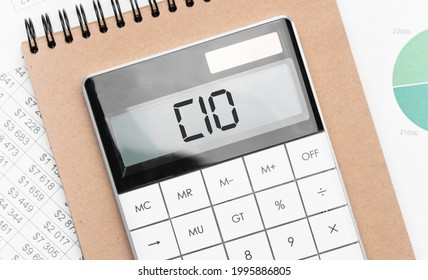 Calculator with text cio with craft colored notepad pen and financial documents.