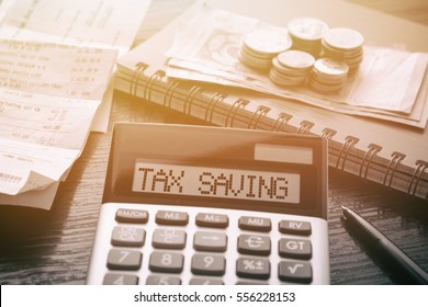 Calculator with text Tax Saving. Calculator, currency, book, bills and pen on wooden table. Business, finance conceptual.