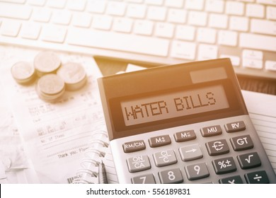 Calculator with text Water Bills. Calculator, currency, book, bills and computer keyboard on wooden table. Business, finance, banking conceptual.