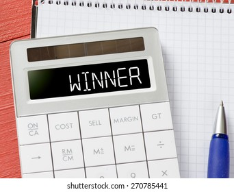 Calculator with winner word. Calculator with winner word and notepad, pen on background
