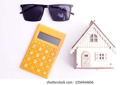 Calculator, wooden house and shade on white background. House building, buying or renting new home planning concept.
