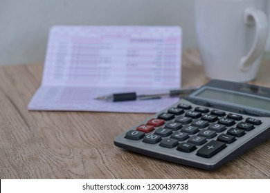 calculator,pen , bankbook ,coffee cup  Put on a wooden table.
