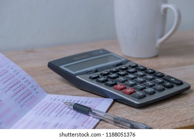 calculator,pencil , bankbook ,coffee cup  Put on a wooden table.