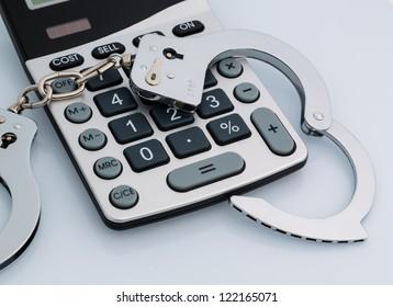 calculators and handcuffs on a white background. representative photo of white-collar crime