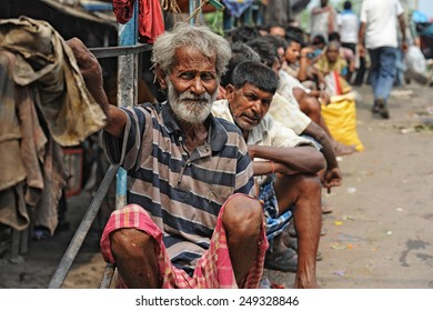 CALCUTTA - APRIL 13: Poor and jobless men waiting on the street for a job on April 13, 2014 in Calcutta, India. India has the largest number of people living below the poverty line of $1.25 per day.