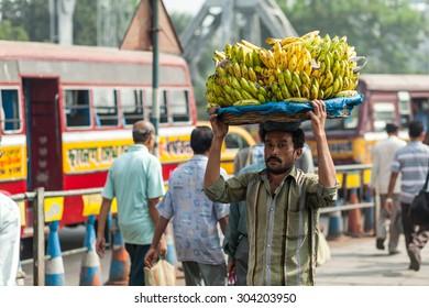 CALCUTTA, INDIA - NOVEMBER 20, 2014: Indian man carrying heavy banana brunches on his head. Flower market, Kolkata, India.