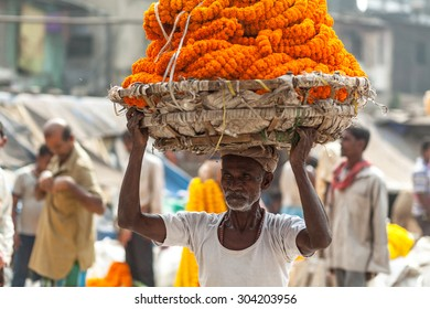 CALCUTTA, INDIA - NOVEMBER 20, 2014: Indian man carrying the heavy basket with flowers on his head. Flower market, Kolkata, India.