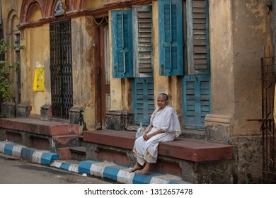 Calcutta (Kolkata), India-January 21, 2019: Traditionally dressed old woman sitting in front of her colorful house in the narrow streets of Calcutta.