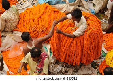 CALCUTTA - OCTOBER 14: An unidentified flower seller buys marigold garlands from a wholesaler on October 14, 2010 in Calcutta, India. The garlands are in very high demand during Diwali festival.