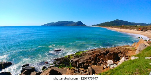 Caldeirao and Armacao beaches in Florianopolis, Brazil, during a sunny morning. Rocks can be seen close to the photographer, and mountains can be seen far away.