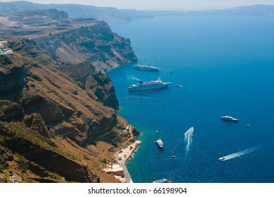 Caldera view on island of Santorini, Greece in Aegean sea with big and small commercial passenger ships.