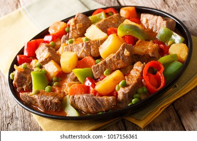 Caldereta ( Kaldereta) beef with potatoes, pepper, peas, tomatoes and carrots in a spicy sauce close-up on a plate on a table. horizontal