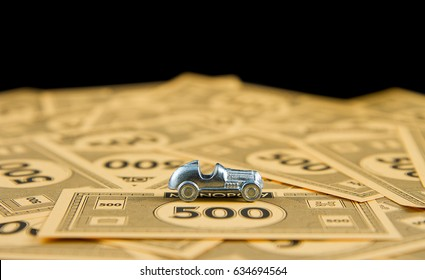 CALDWELL, IDAHO/USA - APRIL 25, 2107: Car from the game of Monopoly up against a stack of bills