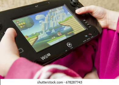 CALDWELL, IDAHO/USA - FEBRUARY 15, 2014: Girl holding a Wii U gamepad while playing Super Mario Bros. U