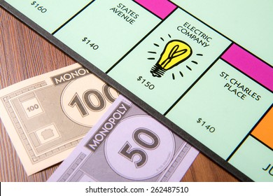 CALDWELL, IDAHO/USA - MARCH 16, 2015: 150 being paid to the Electric company in Monopoly