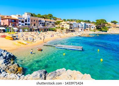 CALELLA DE PALAFRUGELL, SPAIN - JUN 1, 2019: People in water on beach in beautiful scenic village of Calella de Palafrugell, Costa Brava, Spain.