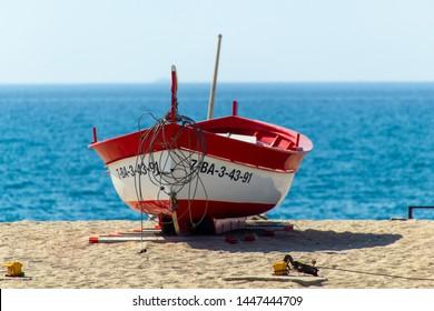 CALELLA, SPAIN - MAY 26, 2011: Red rowboat at the sea