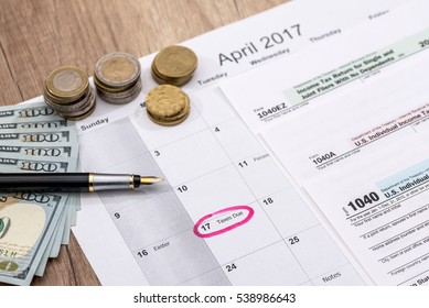 calendar, 2017 tax forms with pen and dollars.