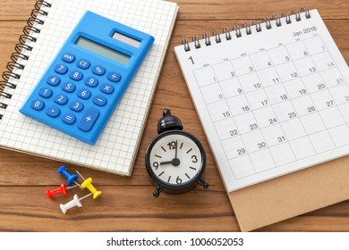 Calendar 2018 with calculator and clock on wooden table