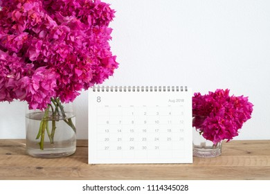 Calendar August 2018 with pink flower bouquet on wooden table