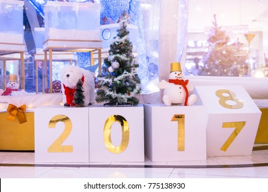 Calendar change to 2018. Atmospheric Christmas and new year decoration. Lights and lighted ornaments glowing in the night, house yard covered with snow.