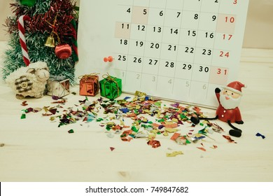 calendar with christmas day decoration equipment placed on wooden table included santa claus, christmas tree, gift boxes, color paper. image for christmas event, happy new year, festival concept