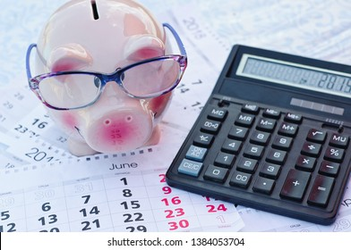 Calendar date for End of Financial Year, for Australian tax year or retail stocktake sales, with piggy bank and pink calculator on sky blue background, with copy space.