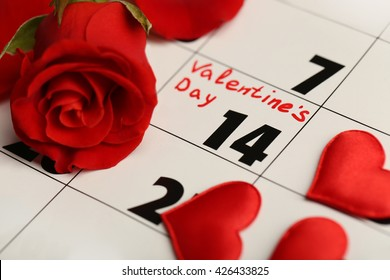 Calendar with date of February 14 and rose flower petals. Valentines day concept