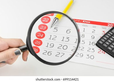 Calendar Days Looking Through Magnifying Glass Hold By Hand With Calculator And Pen Aside