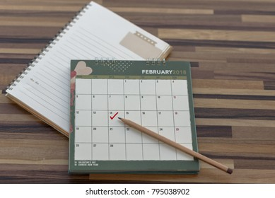 Calendar February 2018 with mark on 14 Valentines day with open Diary pencil notebook on wooden table. Planning scheduling agenda Event organizer writing detail plan for Valentines. Calendar Concept.