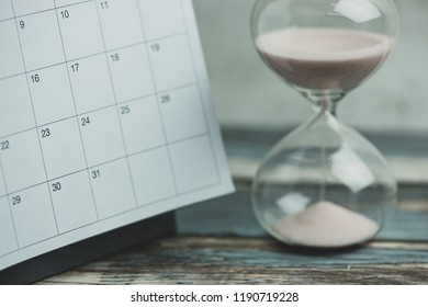 Calendar and hourglass on wood table, vintage style.