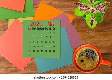 calendar image for May 2020.Coffee, flowers and multicolored pieces of paper on the boards