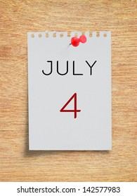 Calendar July 4 on white torn paper note with red pushpin on plywood board