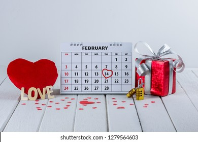 "Calendar page with red hand written heart highlight on February 14 of Saint Valentines day with Couple Combination golden padlock and red Heart shape, Gift box, Wooden letters word ""LOVE"""