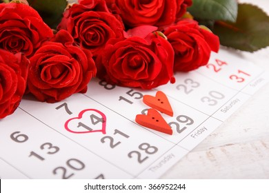Calendar page with the red hearts  and  bouquet of red roses on February 14 of Saint Valentines day.