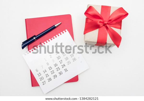 Calendar, pen and notebook, white desktop, gift with red ribbon, copy space, for recording, close up, top view