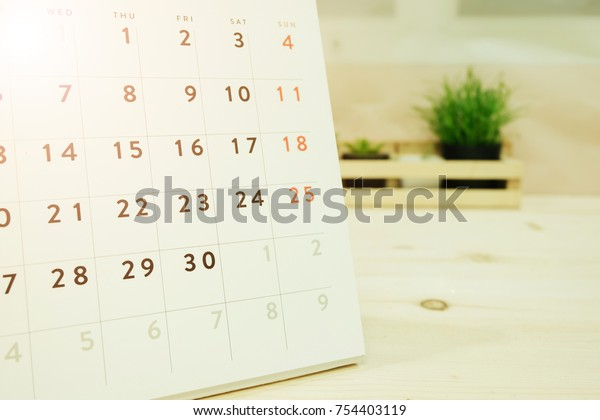 calendar placed on wooden table has ornamental plants in wooden basket are background. image for business, object, decorated, equipment, education concept
