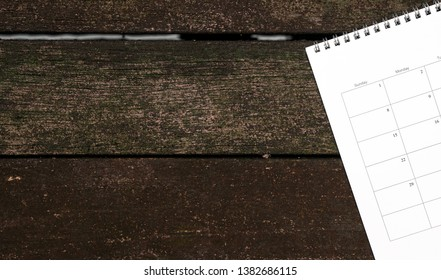 Calendar or planner on dark wood background with copy space. Business schedule concept.