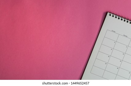 Calendar or planner on pink background with copy space. Business schedule concept.