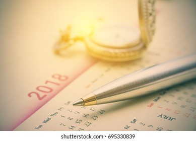Calendar planner stationery concept : Blue metal pen on a paper desk calendar. A calendar is a system of organizing days for commercial or administrative purposes by giving names to a period of time.