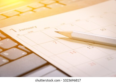 Calendar planner / timetable or schedule arrangement concept : Top view of a silver pencil on a flipped paper / desk calendar. A calendar is a system of organizing days for administrative purposes.