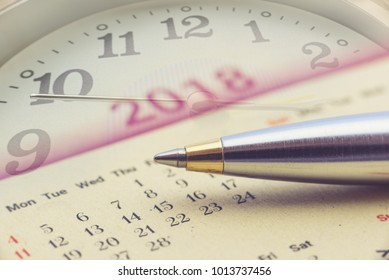 Calendar planner for year 2018 concept : Blue metal pen on a paper desk calendar with analog clock and a clock hand, depicts the passing of time, planning or making time schedule for future project.