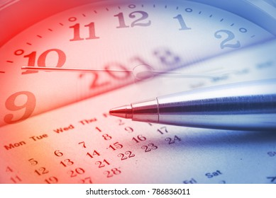 Calendar planner for year 2018 concept : Blue metal pen on a paper desk calendar with analog clock and a clock hand, implies the passing of time, planning or making time schedule for future project.